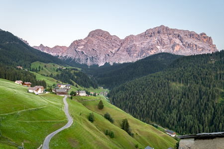 Peaks of the Dolomites in South Tyrol during the sunset, the valley with sinous roads and a small settlement in the foreground. The peaks from left to right are Cima Nove, Top Ten and Monte Cavallo