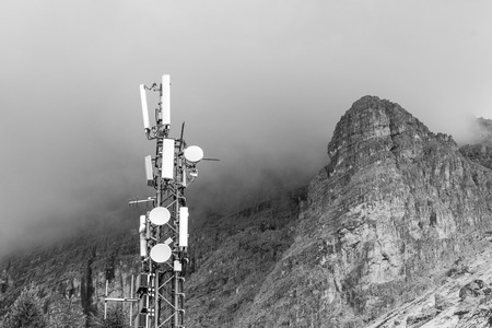 Transmitter station in black and white on top of a mountain with storm clouds gathering around a mountain peak in the background. Concept of interference in the broadcast Stock Photo