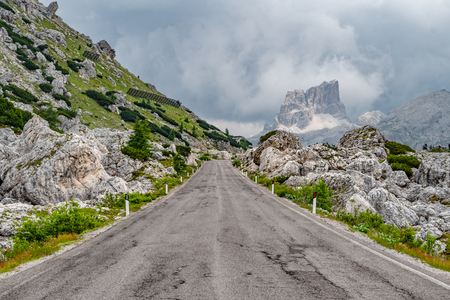 Empty deserted road leading to the stormy, cloudy rocky mountains of the Dolomites, Italy