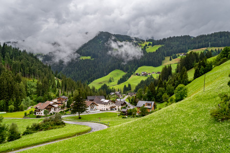 Sinous road leading to a cloudy valley with green hills and pine forests in La Valle, South Tyrol, Italy