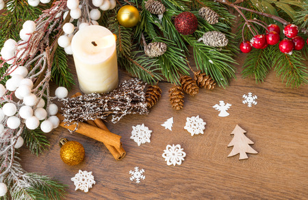 Christmas candle and decoration on a brown wooden surface with snowflakes, fir, red berries, christmas ornaments, pine cones and cinnamon sticks