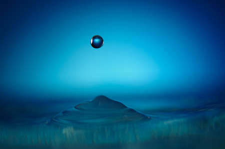 One blue water drop forming abstract figure without splashes photo