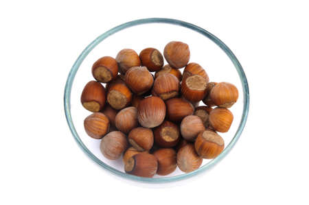 Fistful of brown hazel nuts in the glass cup isolated photo