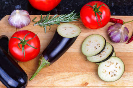 Set of vegetables on cutting board, eggplant, garlic, tomatoes, rosemary, chili pepper photo