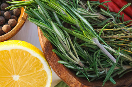 ingridients: Vegetables and herbs as ingridients for chicken dish recipe: rosemary, lemon, allspice, thyme and chili pepper in round  plates Stock Photo