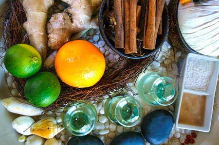 lyme: Top flat view of spa ingredients: oil in glass jars, orange, lyme, ginger, cinnamon sticks, stones, sand. Spa concept