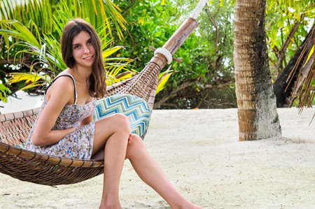 likeable: Young lady relaxing in hammock on tropical beach