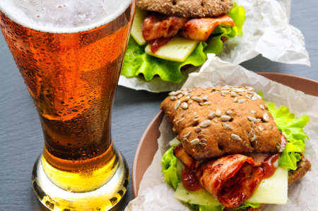 paper plates: Glass of beer and two burger-like sandwiches with lettuce, bacon, cheese, ketchup on paper, plates and black slate stone Stock Photo