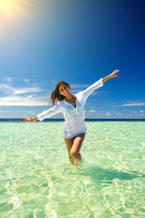 water wings: Young slim woman playing in the clean sea water making airplane wings. Summer vacation concept