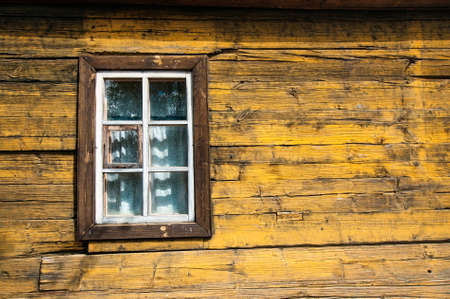 timbered: Yellow timbered wooden loghouse wall with window