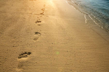 sunspot: Footprints on sand along sea shore and golden sunset