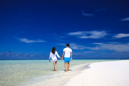 Back view of young couple on white beach. Vacation romantic concept