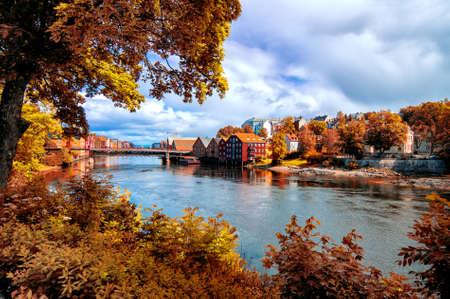View through autumn foliage to Nidelva river, Trondheim city, Norway Stock Photo