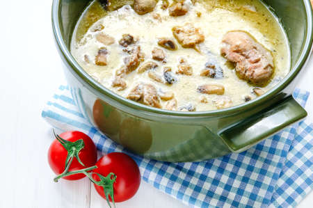 Fricassee of chicken with mushrooms in ceramic pot on white wooden table