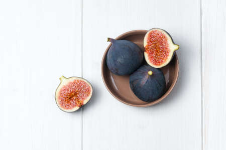 Top flat view: fresh figs on white wooden background