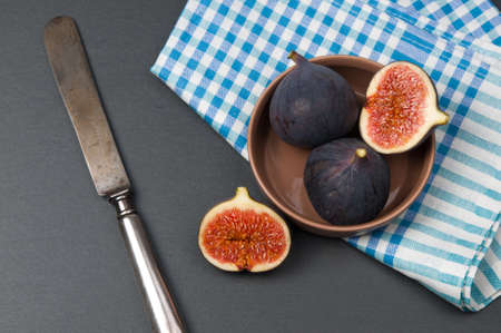 Sliced fig fruits in ceramic bowl and vintage knife on black stone