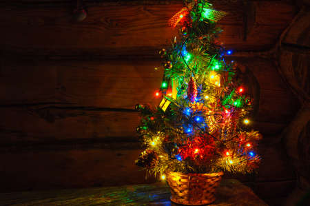 Small Christmas Tree With Multi Colored Lights On Rustic Wooden