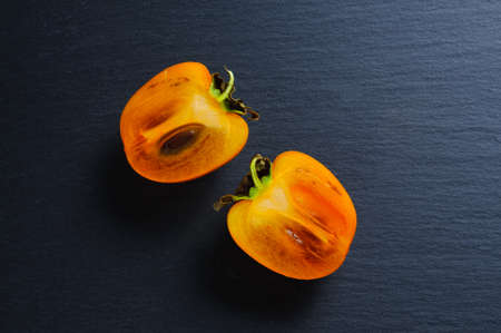 Slices of persimmon on black slate stone background. Top view