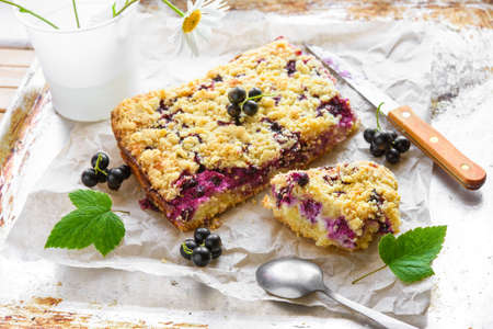 Black currant and cottage crumble cake on baking paper and rustic background