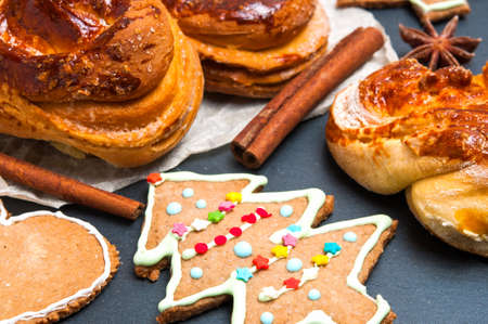 Christmas homemade baked products: pine-shape cookies, cinnamon buns and ingredients Stock Photo