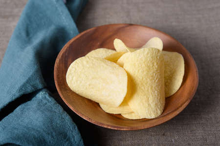 Crispy potato chips in wooden bowl with napkin