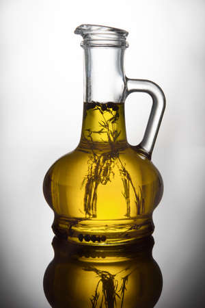 Glass bottle with herbs oil on white background