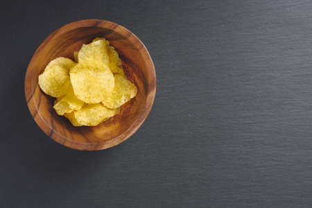 Crispy potato chips in bowl on black background, top view, copy space
