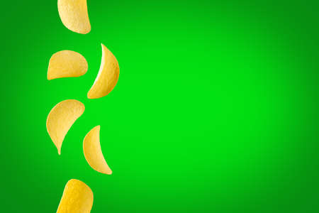 Falling potato chips isolated on green background. Flying crispy snacks Stock Photo