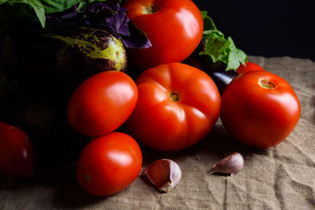 Contrast summer vegetables: red tomatoes and eggplants Stock Photo