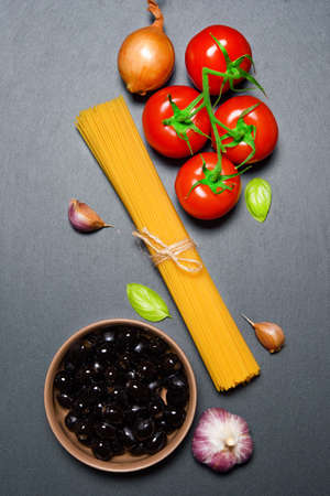 Top view: pasta ingredients on black slate stone background