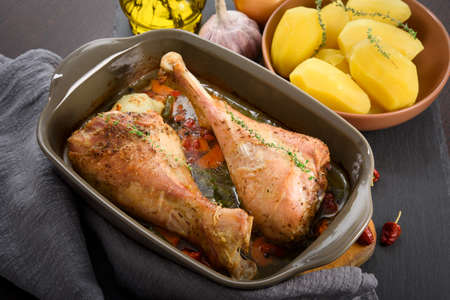 Roasted turkey legs with vegetables, potato and herbs