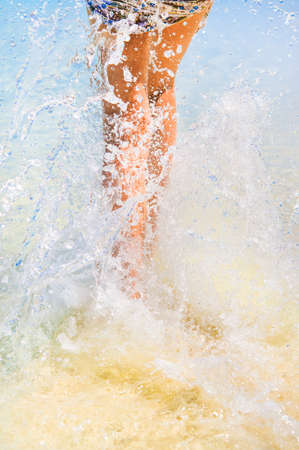 Water splashes made with woman legs on beach. Vacation and summer mood Stock Photo