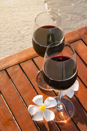 Relaxing beach scene: two glasses of red wine at sunset near water