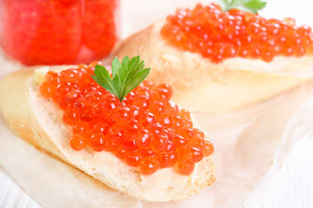 Snacks with red caviar on white paper close-up