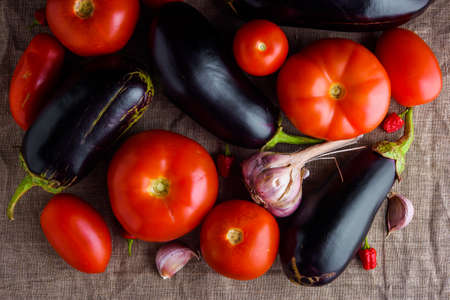 Summer vegetables: fresh red tomatoes, garlic and eggplants