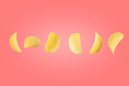 Potato chips isolated on pink background. Flying crispy snacks