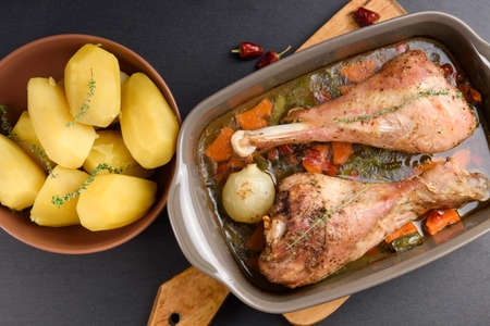 Roasted turkey legs with vegetables, potato and herbs. Top view Stock Photo