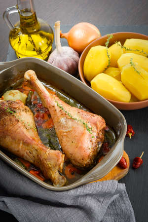 Roasted turkey legs in ceramic bowl with vegetables, potato and herbs Stock Photo