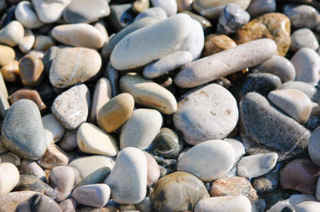Sea gravel shore or beach at sunset