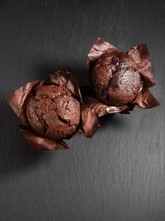 Two chocolate muffins in baked paper on black stone background
