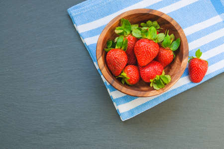 Fresh strawberry in wooden bowl on white blue fabric background