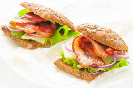 Homemade sandwich with ham bacon, cheese, lettuce and onion on white plate and wooden background
