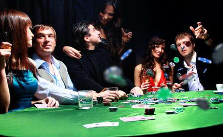 cartas de poker: Joven tirando fichas en la mesa jugando cartas Foto de archivo