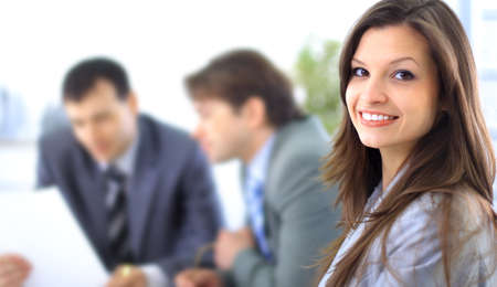 A confident relaxed business woman smiling with her colleagues at the back  Stock Photo - 11146869