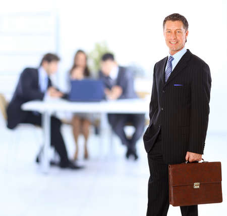 Successful business man standing with his staff in background at office  photo