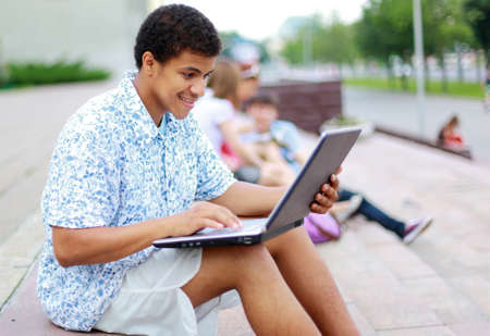 to lap: A smiling african american man on his laptop  Stock Photo