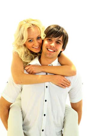 piggy back: Piggybacking - Happy young teenaged couple enjoying themselves against white Stock Photo