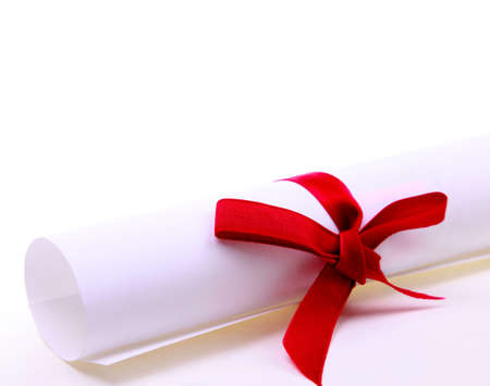 Paper scroll and red bow isolated on white backgrou photo