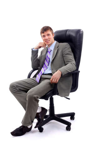 Young businessman sitting on chair against white background photo