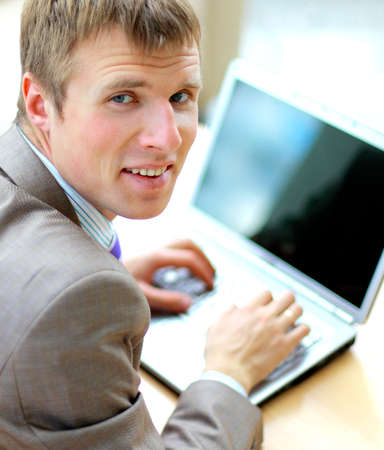 Businessman sitting at desk in office, working with laptop computer, looking back, smiling photo